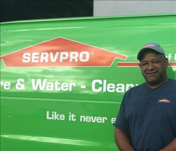 Servpro rep standing in front of a company vehicle